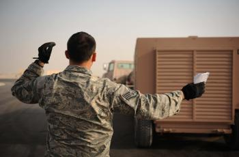 U.S. Air Force Staff Sgt. Walter Towers, 8th Expeditionary Air Mobility Squadron (EAMS) ramp supervisor and native of Vega Baja, Puerto Rico, directs a vehicle operator backing up a generator prior to loading in a U.S. Air Force C-17 Globemaster III cargo aircraft Feb. 11, 2012. Airmen from the 8th EAMS ramp section are trained to load all types of cargo onto aircraft. (U.S. Air Force photo by Staff Sgt. Nathanael Callon)