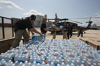 U.S. Customs and Border Protection Air and Marine Operations aircrews and Office of Field Operations officers work together to load water and rations on a CBP black hawk for delivery to victims of Hurricane Harvey.    Photographer: Donna Burton