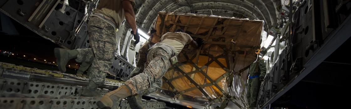 Soldiers offloading a large shipment from a plane.