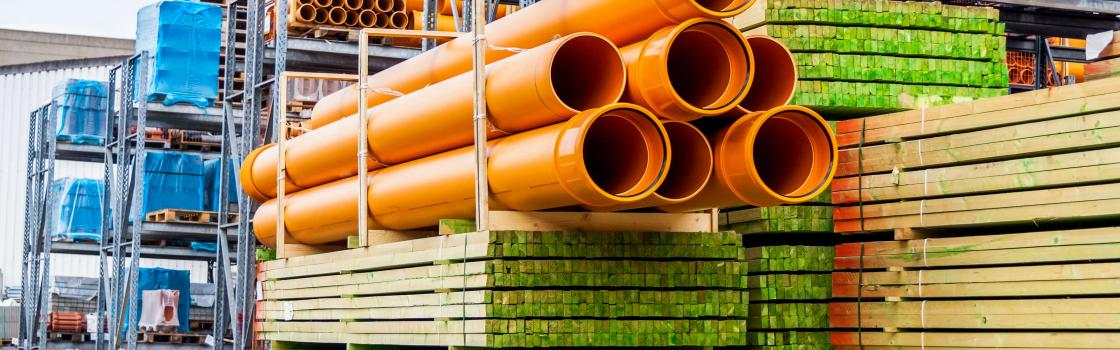 stacked orange pipes and lumber