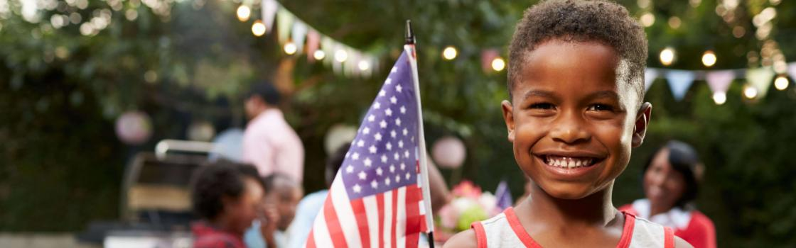 Young boy holding flag at 4th July family garden party