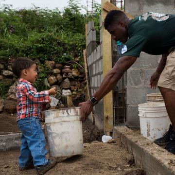 U.S. Marine Corps Sgt. Antoine D. Coleman, the armory chief with the Command Element, Special Purpose Marine Air-Ground Task Force - Southern Command, helps a child carry a bucket of gravel during a community relations event in La Paz, Honduras, Oct. 25, 2017. Partnered with Habitat for Humanity, the Marines worked to build the foundation of a house for a local family. The Marines and sailors of SPMAGTF-SC are deployed to Central America to conduct security cooperation training and engineering projects with