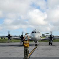 U.S. Navy Petty Officer with the Golden Swordsmen of Patrol Squadron directs a P-3C Orion maritime patrol aircraft to its parking spot in Okinawa, Japan