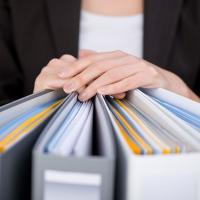 An office worker rests her hands on top of four office binders