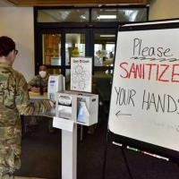 An airman assigned to the 354th Medical Group sanitizes her hands at Eielson Air Force Base
